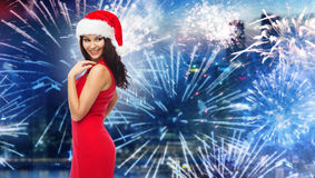 Woman in santa hat and red dress over firework Royalty Free Stock Image