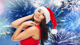 Woman in santa hat and red dress over firework Stock Image