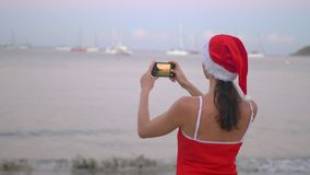 Woman in santa hat and red swimsuit taking photo with smartphone mobile camera on the seashore at sunrise. Smiling modern woman in red swimsuit taking photo with stock video footage