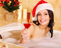 Woman in santa hat relax in bath. Royalty Free Stock Image