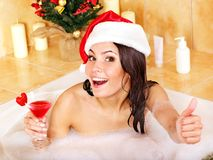 Woman in santa hat relax in bath. Royalty Free Stock Photo