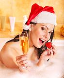 Woman in santa hat relax in bath. Royalty Free Stock Images