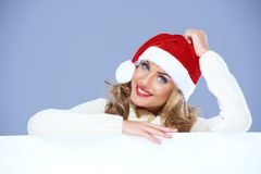 Woman in a santa hat resting on a blank billboard Royalty Free Stock Image