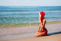Woman in santa hat on the sea beach. Stock Images