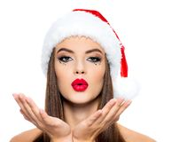 Woman in a santa hat sends a kiss. Beautiful woman`s face with palms near face with kissing sign - isolated on white background. stock photography
