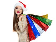 Woman in santa hat with shopping bags. stock images