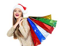 Woman in santa hat with shopping bags. Young cheerful woman stock image