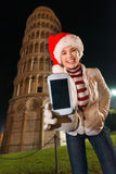 Woman in Santa hat showing mobile phone near Leaning Tower, Pisa Royalty Free Stock Photo