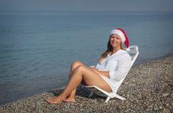 Woman. In santa hat sitting on the beach Stock Photos