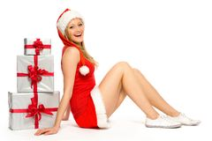 Woman in Santa hat sitting near Christmas presents Royalty Free Stock Image