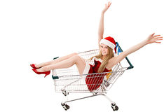 Woman in santa hat sitting in shopping cart Stock Images
