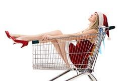 Woman in santa hat sitting in shopping cart Royalty Free Stock Photos