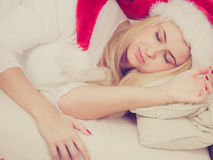 Woman in Santa hat sleeping on couch Royalty Free Stock Photo