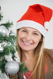 Woman In Santa Hat Smiling By Christmas Tree Stock Images