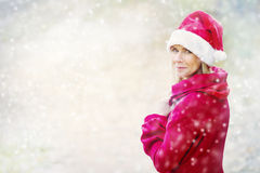 Woman in Santa hat standing outside in the snow Stock Image
