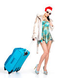 Woman in santa hat  standing with travel suitcase Royalty Free Stock Photo