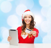 Woman in santa hat with tablet pc and credit card Royalty Free Stock Image