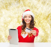 Woman in santa hat with tablet pc and credit card Stock Photos