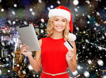 Woman in santa hat with tablet pc and credit card Royalty Free Stock Photography
