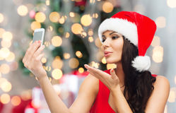 Woman in santa hat taking selfie by smartphone Royalty Free Stock Images