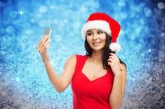 Woman in santa hat taking selfie by smartphone Royalty Free Stock Photos