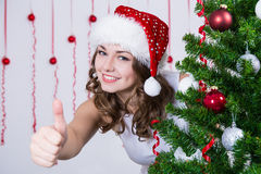 Woman in santa hat thumbs up near Christmas tree Stock Photos