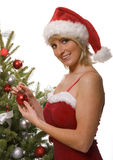Woman in Santa hat by tree Royalty Free Stock Images