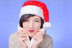 Woman in santa hat under snowflakes Royalty Free Stock Photos