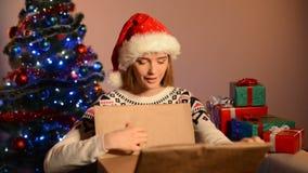Woman in Santa hat unpacking Xmas gift stock video