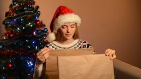 Woman in Santa hat unpacking Xmas gift stock footage