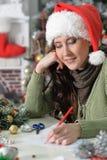 Woman in Santa Hat writing letter. Portrait of young woman in Santa Hat writing letter Stock Photos