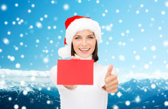 Woman in santa helper hat with blank red card Royalty Free Stock Photos