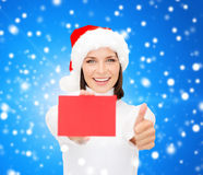 Woman in santa helper hat with blank red card Royalty Free Stock Image