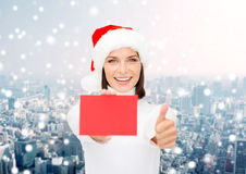 Woman in santa helper hat with blank red card Stock Images