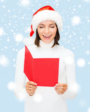 Woman in santa helper hat with blank red postcard Stock Images