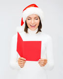Woman in santa helper hat with blank red postcard Stock Photo