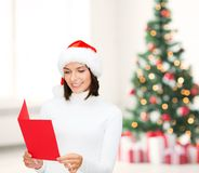 Woman in santa helper hat with blank red postcard Royalty Free Stock Images