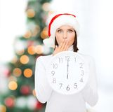 Woman in santa helper hat with clock showing 12. Christmas, x-mas, winter, happiness concept - smiling woman in santa helper hat with clock showing 12 Stock Photography