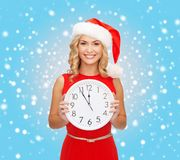 Woman in santa helper hat with clock showing 12. Christmas, x-mas, winter, happiness concept - smiling woman in santa helper hat with clock showing 12 Royalty Free Stock Image