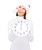 Woman in santa helper hat with clock showing 12 Stock Photography