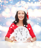 Woman in santa helper hat with clock showing 12 Stock Image