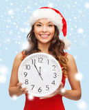 Woman in santa helper hat with clock showing 12 Stock Photos