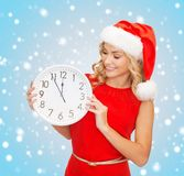 Woman in santa helper hat with clock showing 12 Royalty Free Stock Photo