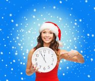 Woman in santa helper hat with clock showing 12 Royalty Free Stock Images