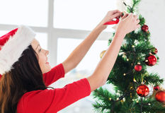Woman in santa helper hat decorating a tree Royalty Free Stock Photography