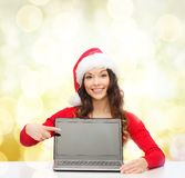 Woman in santa helper hat with laptop computer Stock Image