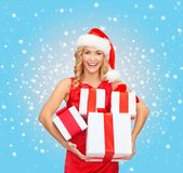 Woman in santa helper hat with many gift boxes Stock Photos