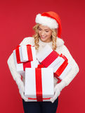Woman in santa helper hat with many gift boxes Stock Image
