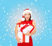 Woman in santa helper hat with many gift boxes Royalty Free Stock Photos