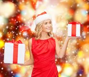 Woman in santa helper hat with many gift boxes Stock Photo